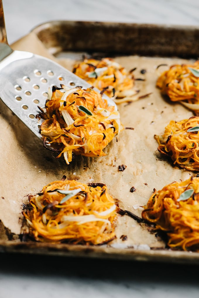A baking sheet filled with butternut squash and sweet potato fritters with a spatula removing one fritter.