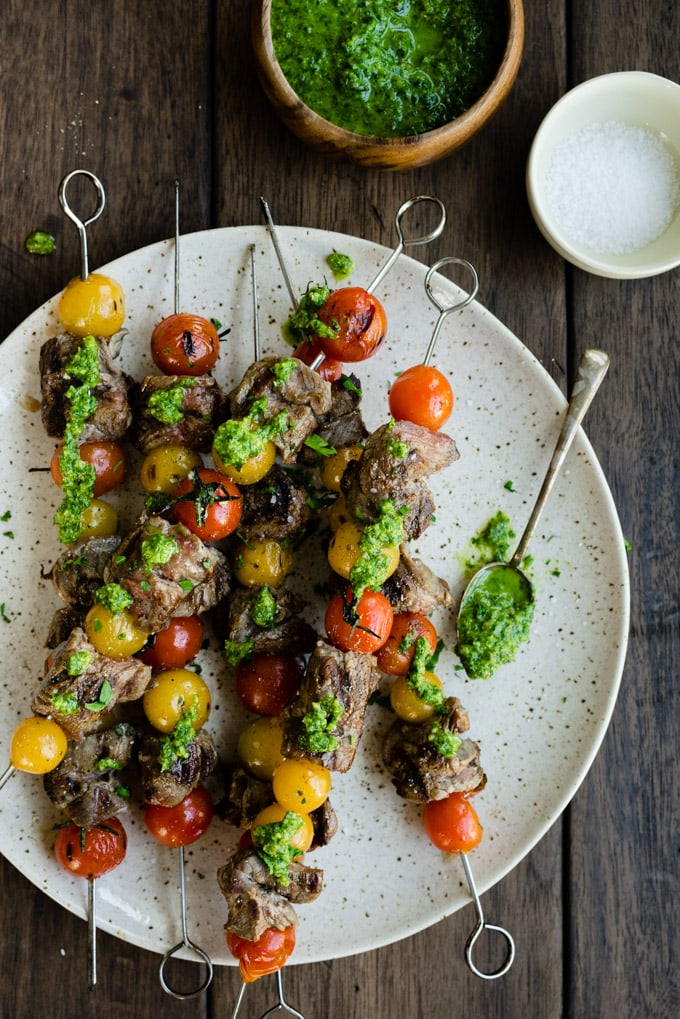 A platter of grilled flank steak skewers drizzled with paleo parsley pesto on a wood table.