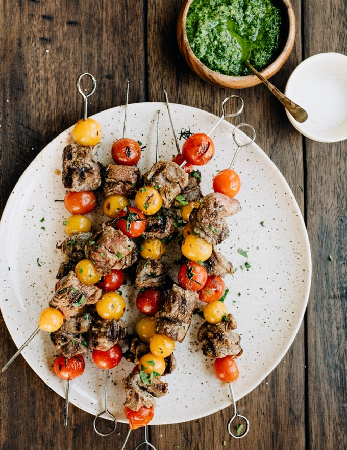 A platter of grilled steak skewers with tomatoes and a side of dairy free parsley pesto.