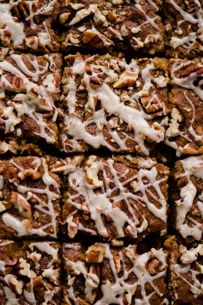 A tray of healthy pumpkin bars drizzled with vanilla glaze sliced into squares.