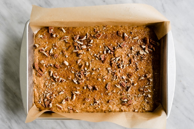 A cake pan lined with parchment paper, filled with healthy pumpkin bar batter, topped with chopped pecans.