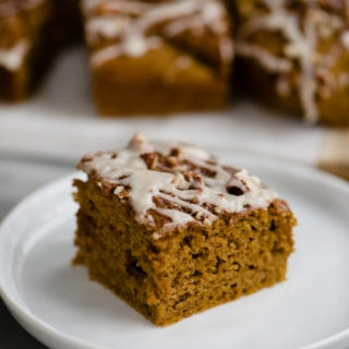 A healthy pumpkin bar with pecans and vanilla glaze on a dessert plate.
