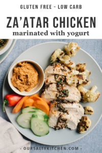 A plate of yogurt marinated za'atar chicken with roasted cauliflower, muhammara dipping sauce, and sliced raw vegetables.