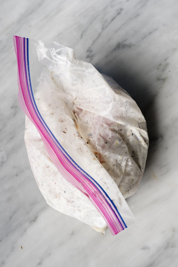 Raw chicken breasts marinated with yogurt, lemon, and za'atar spice in a gallon sized ziplock bag.