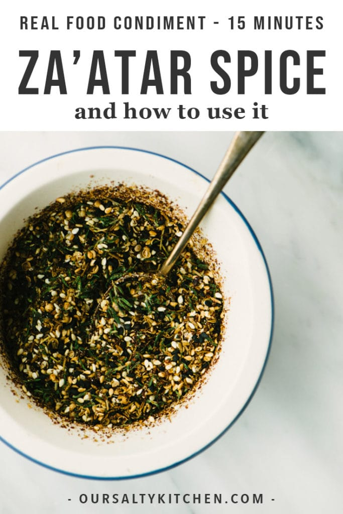 A bowl of homemade za'atar spice in a mortar with a small serving spoon on a marble table.