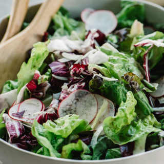 A tossed green salad in a bowl with butter lettuce, radicchio, fennel, and radishes.