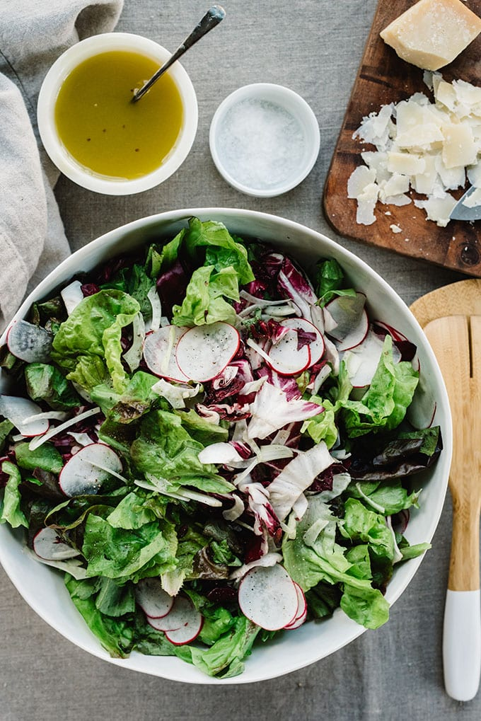 A tossed green salad of butter lettuce, radicchio, fennel, and radishes in a large white bowl with parmesan cheese and champagne vinaigrette on the side.