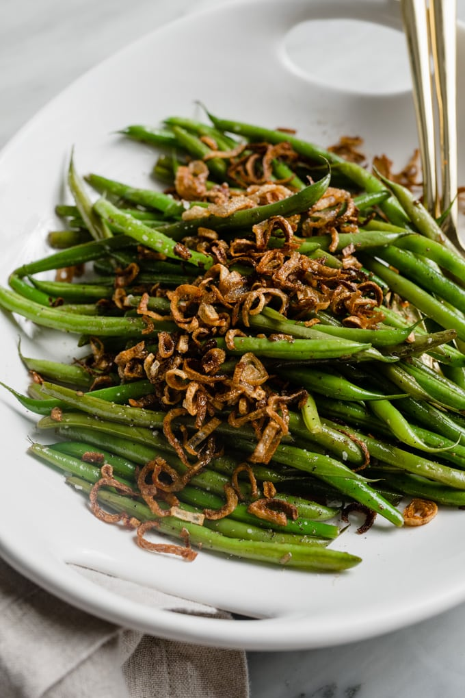 A dish of garlicky green beans topped with crispy shallots.