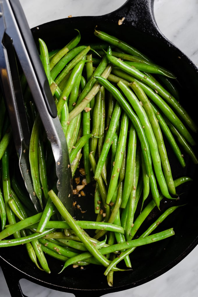 Green beans sautéed with garlic in a cast iron skillet.