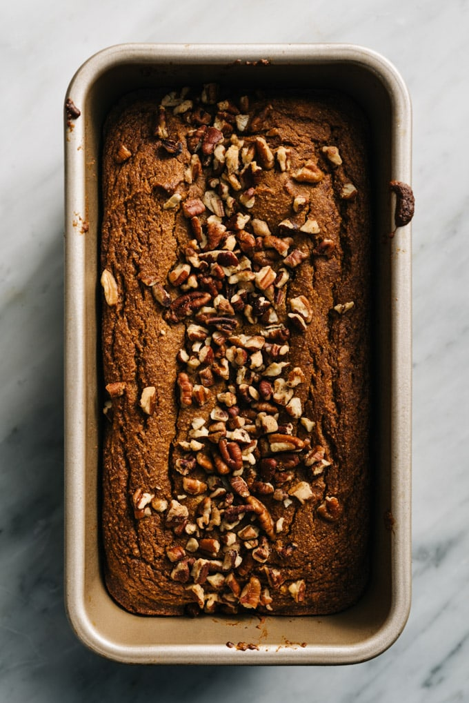 A loaf of freshly baked paleo pumpkin bread cooling in a bread pan.