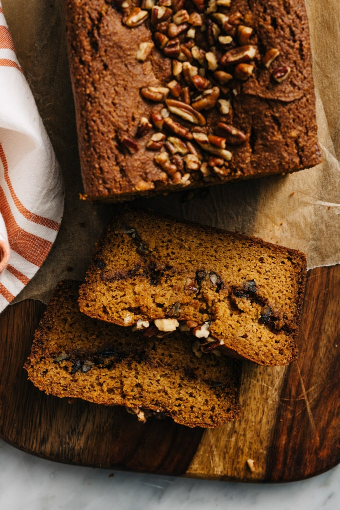 Two slices of paleo pumpkin bread on a cutting board with an orange and white tea towel.