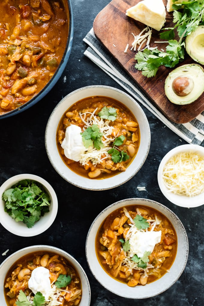 Several bowls of pumpkin chicken chili surrounded by toppings and garnishes such as avocado, sour cream, sharp cheddar and cilantro.