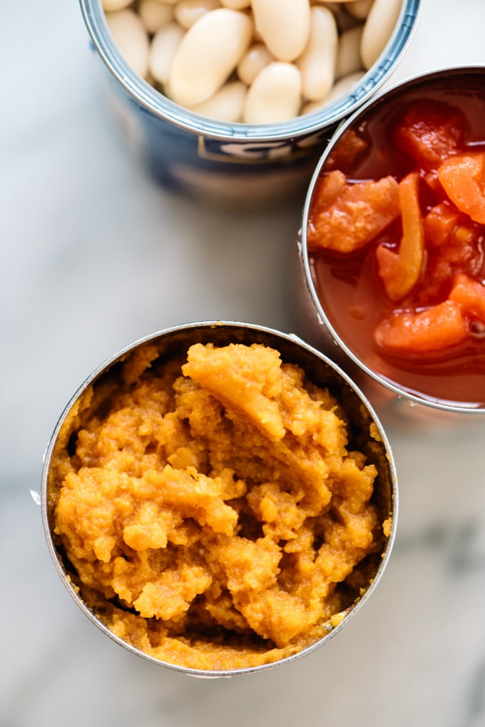 Three open cans of pumpkin puree, diced tomatoes, and white beans.