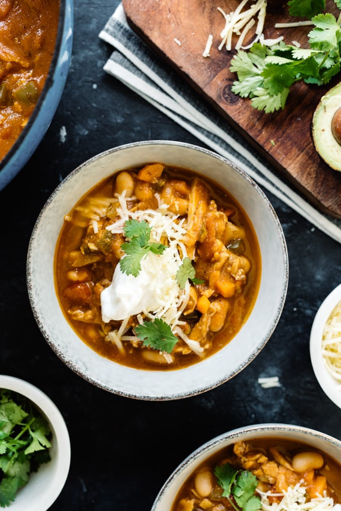 A bowl of gluten free pumpkin chicken chili on a black surface surrounded by small bowls of toppings.