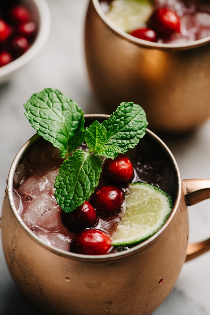 A cranberry moscow mule cocktail garnished with mint, fresh cranberries, and a lime wedge on a marble table.