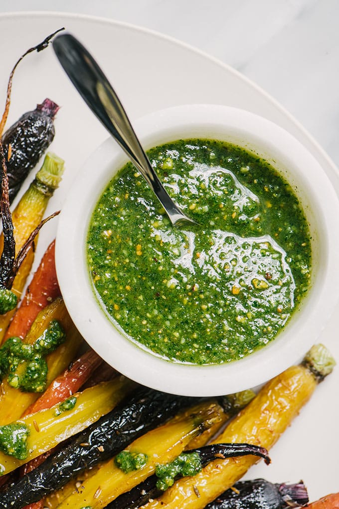 Carrot green pesto in a white marble bowl on a platter surrounded with honey roasted carrots.