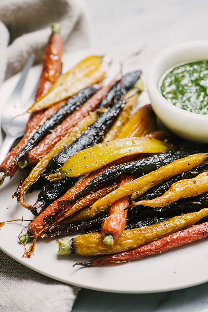 A white plate filled with honey roasted carrots and a small bowl of carrot green pesto.