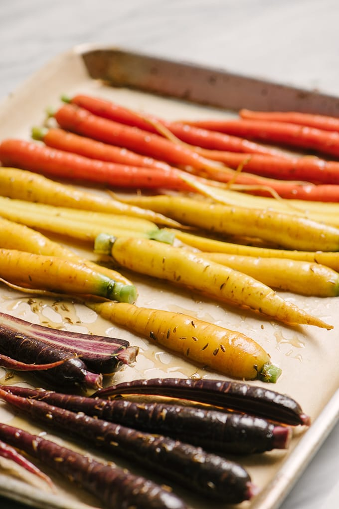 Tri-color carrots tossed with honey and cumin on a baking sheet.