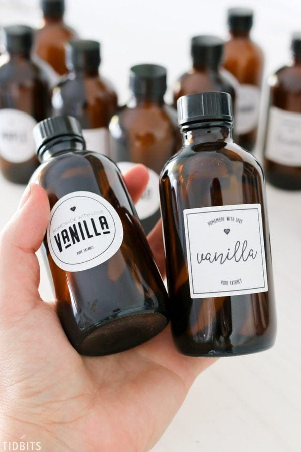 A woman holding two small jars of instant pot vanilla extract, the perfect made in advance edible Christmas gift!