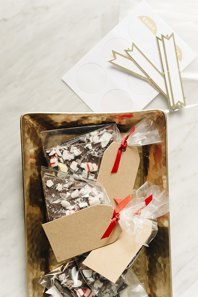 Homemade chocolate bark edible Christmas gift wrapped in pretty packaging on a gold tray.