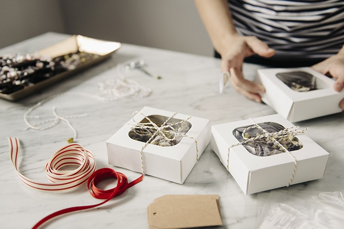 A woman wrapping edible Christmas gifts in pretty boxes with ribbons.