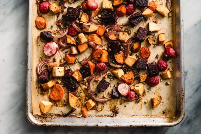 Roasted root vegetables with maple syrup, thyme, and pecans on a baking sheet.