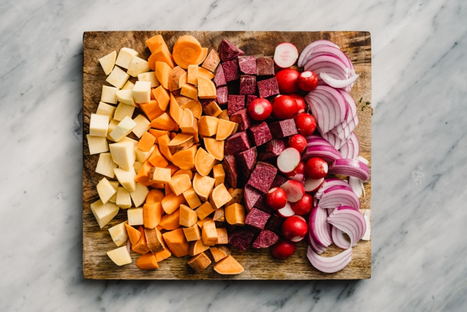 Various root vegetables, including diced parsnips, carrots, sweet potatoes, radishes, and red onions on a cutting board.