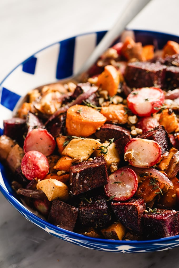 Maple roasted root vegetables in a blue serving bowl sprinkled with pecans and fresh thyme.