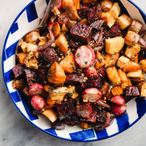 Maple roasted root vegetables in a blue and white bowl with fresh thyme and chopped pecans.