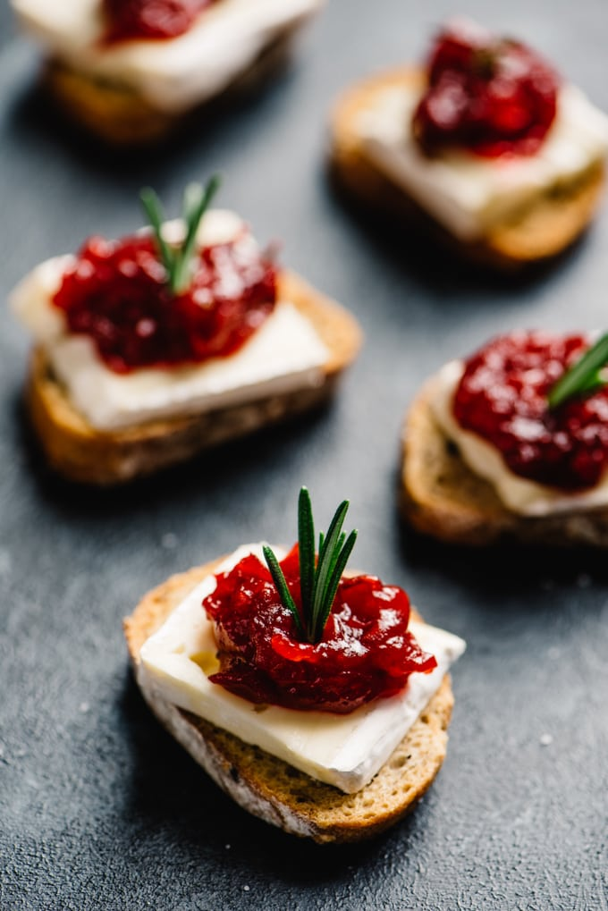 Cranberry brie bites cocktail appetizer spread - toasted baguettes topped with a slice of brie, cranberry jam, and a sprig of rosemary garnish.