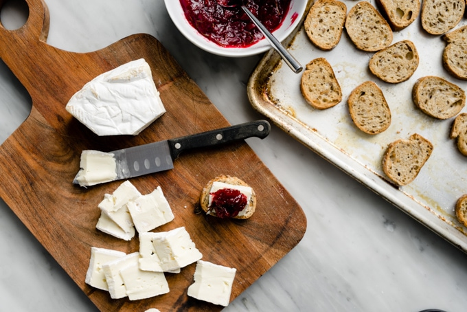 A bowl of cranberry jam, toasted baguettes on a baking sheet, and slices of brie cheese on a cutting board with one composed cranberry brie bite.