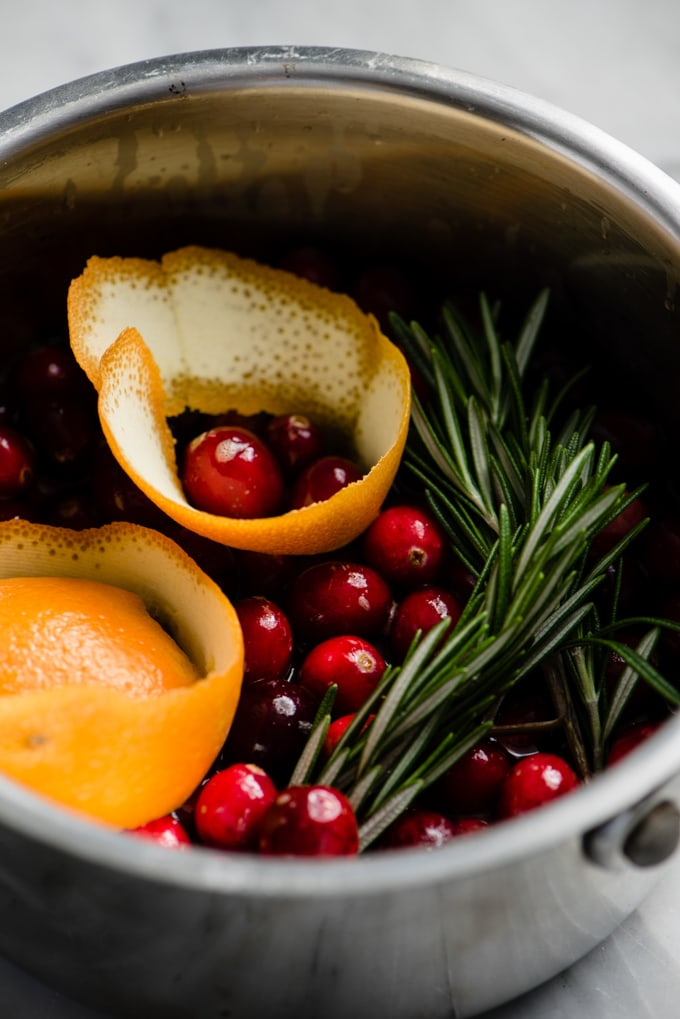 Fresh cranberries, brown sugar, orange zest, and fresh rosemary in a small pot for making homemade cranberry jam.