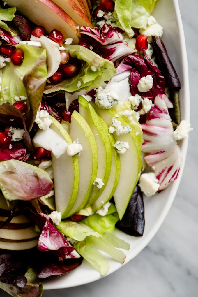 A close up image of a platter of winter chopped salad with pear, endive, and pomegranate.