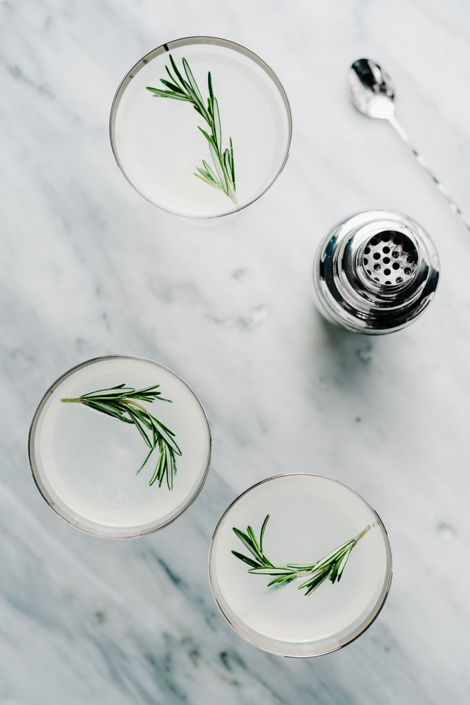 An overhead view of three rosemary vodka gimlet cocktails on a marble table with a silver cocktail shaker.