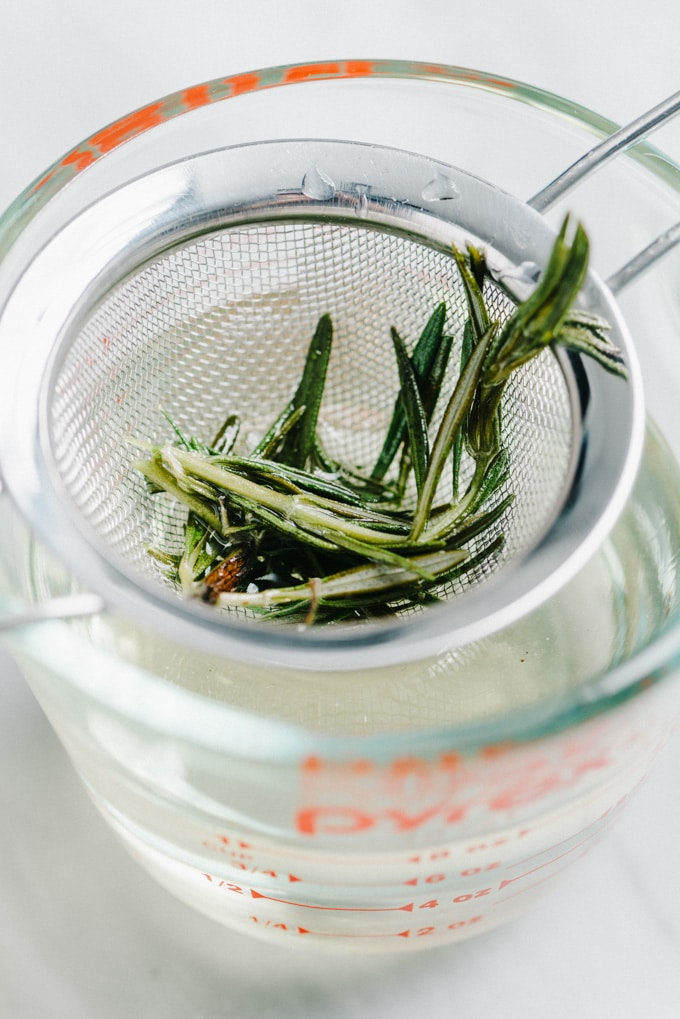 Rosemary infused simple syrup being strained through a fine mesh sieve into a glass jar.