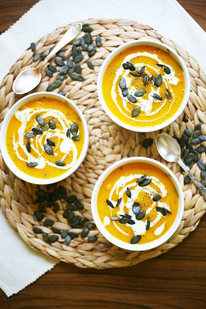Three bowls of hokkaido pumpkin whole30 soup garnished with pumpkin seeds on a round woven mat.