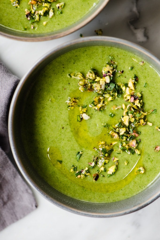 A bowl of spinach and potato whole30 soup garnished with pistachio gremolata.