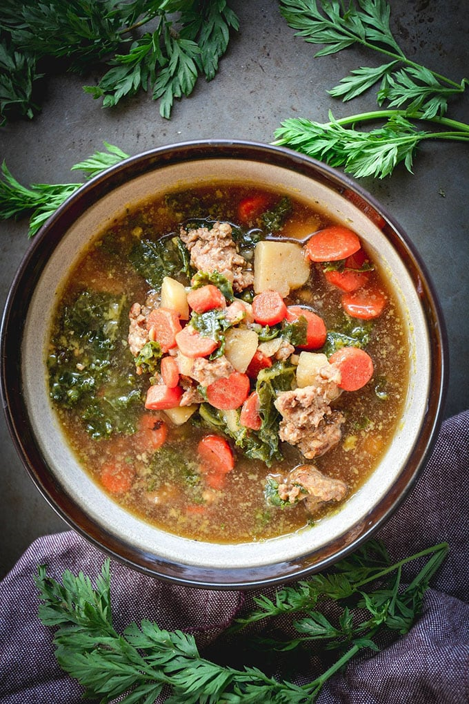 Sausage, kale, and carrot whole30 soup in a brown iand white bowl with a side of fresh herbs.
