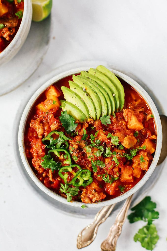 A bowl of easy sweet potato whole30 chili garnished with avocado, cilantro, and jalapeno on a marble background.