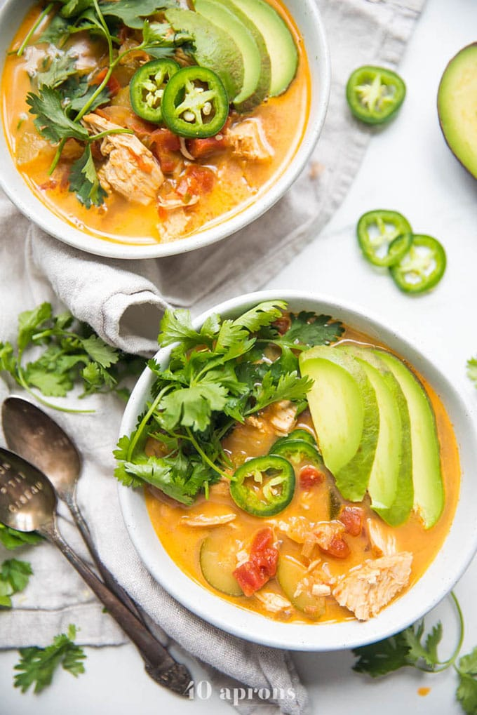 Two bowls of chicken tortilla less soup with avocado, cilantro and jalapeno on a marble table.