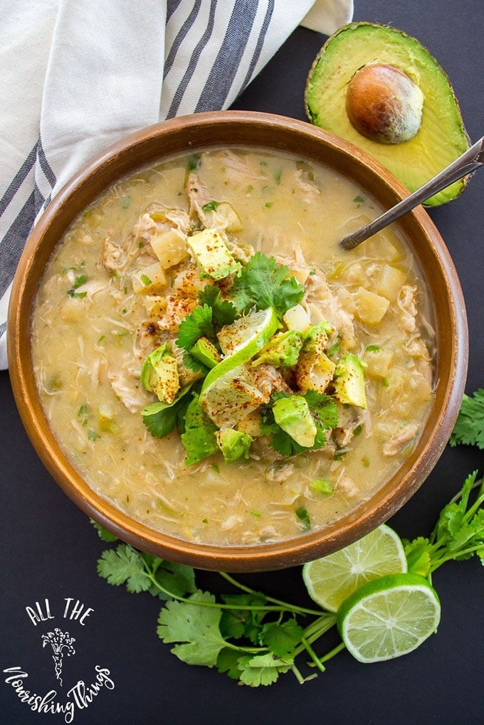 Green chicken chili whole30 soup in a brown bowl with avocado, lime, and cilantrol