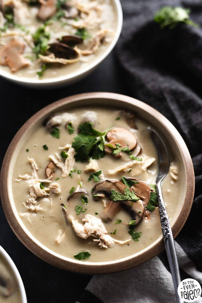 A bowl of creamy chicken and mushroom whole30 soup garnished with fresh parsley.