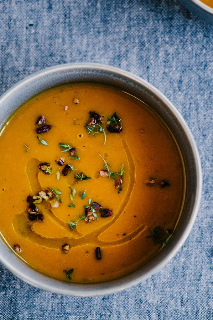A bowl of carrot and apple whole30 soup garnished with pecans and thyme on a blue tablecloth.