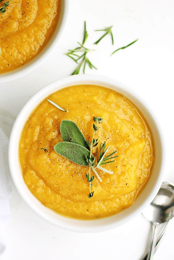 Golden potato and butternut squash whole30 soup in a white bowl garnished with fresh herbs.