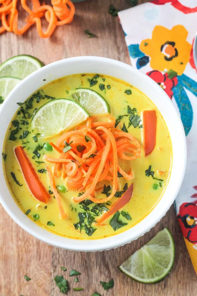 Coconut curry whole30 soup with sweet potato noodles in a white bowl on a wood background.