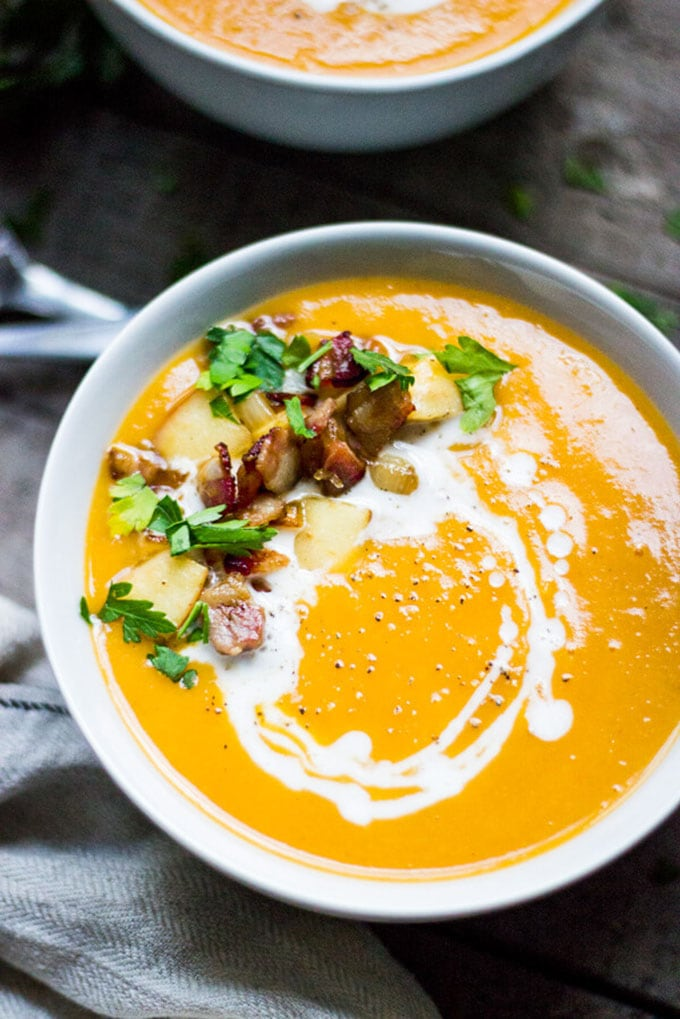 Creamy butternut squash whole30 soup garnished with bacon and apple.