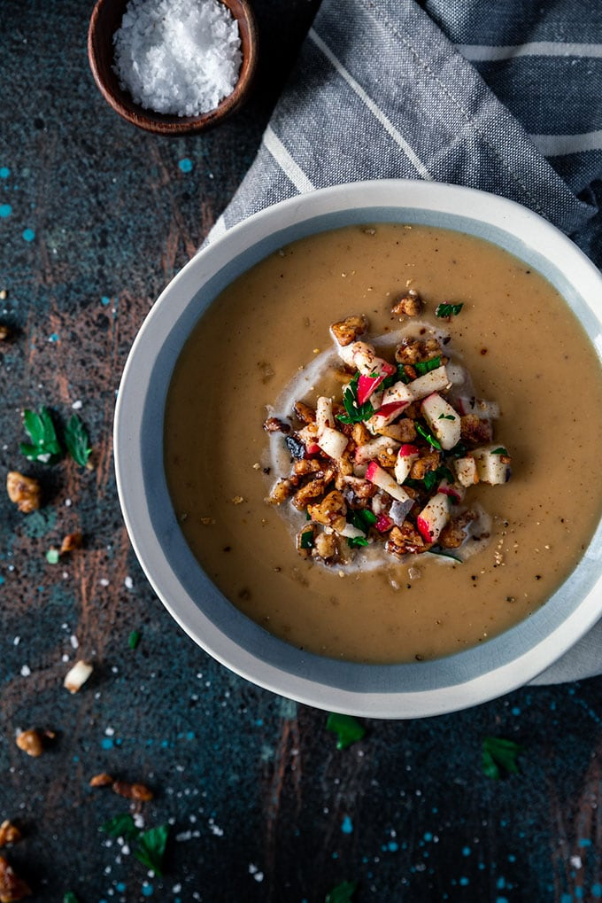 A bowl of creamy moroccan spiced parsnip whole30 soup on a dark background garnished with apples and za'atar spice.