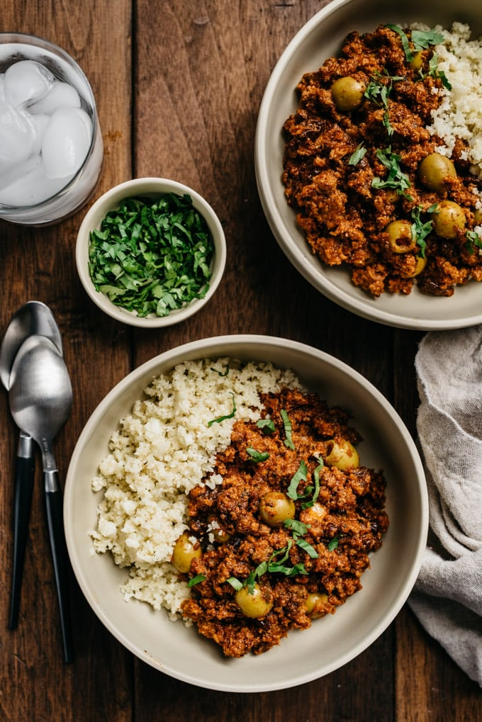 Two bowls of Whole30 picadillo over cauliflower rice with fresh cilantro on a wood table.
