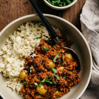 A whole30 picadillo recipe in a tan bowl served with cauliflower rice and cilantro on a wood table.