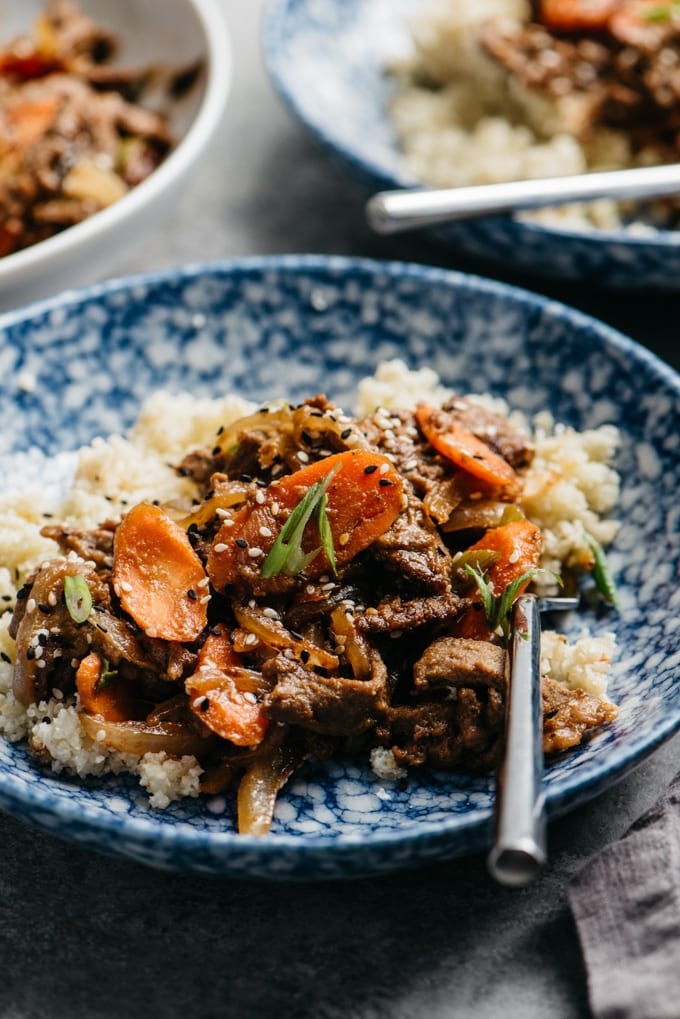 A bowl of healthy Whole30 beef bulgogi over cauliflower rices in a blue bowl with a silver fork.